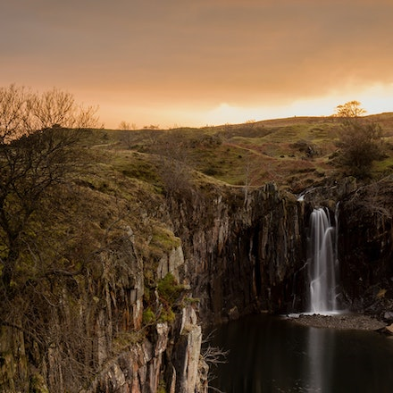 A quarry a waterfall and a sunset